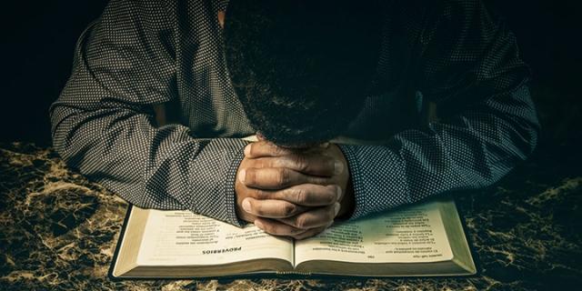 Man praying to God on an open Bible